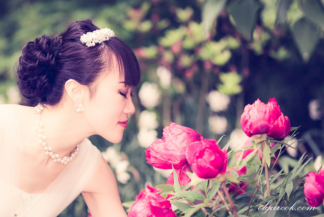 portrait of a Chinese bride smelling peony flowers