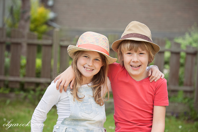 colourful portrait of little brother and sister wearing hats and laughing: the photo has an idyllic countryside mood
