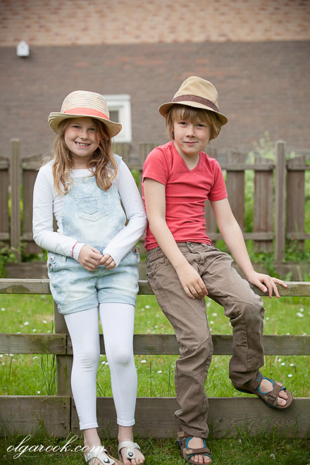 portrait of a little girl and a boy sitting on a fence next to each other.