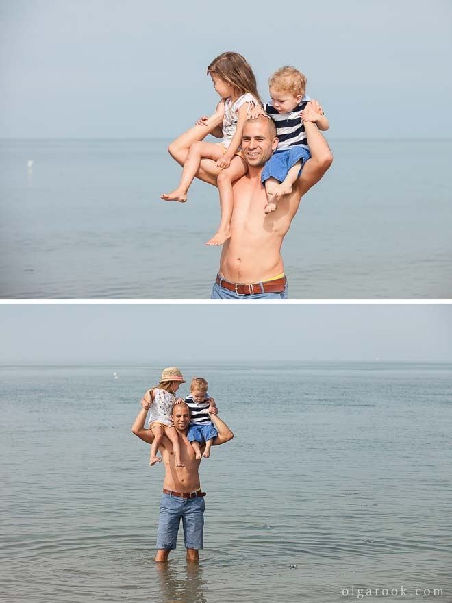 Photo at the sea: an athletic father is holding his little children on his shoulders.