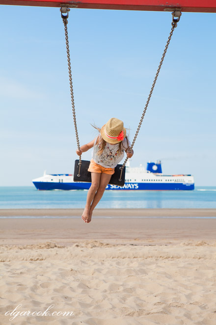Happy and nostalgic photo of a little girl on a swing on a beach