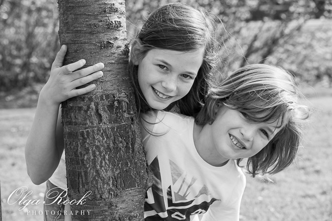 black and white photo of a little sister and brother playing together in a park