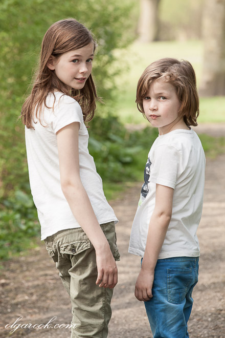 photo of two kids on a path in a park looking back with a tough expression on their faces
