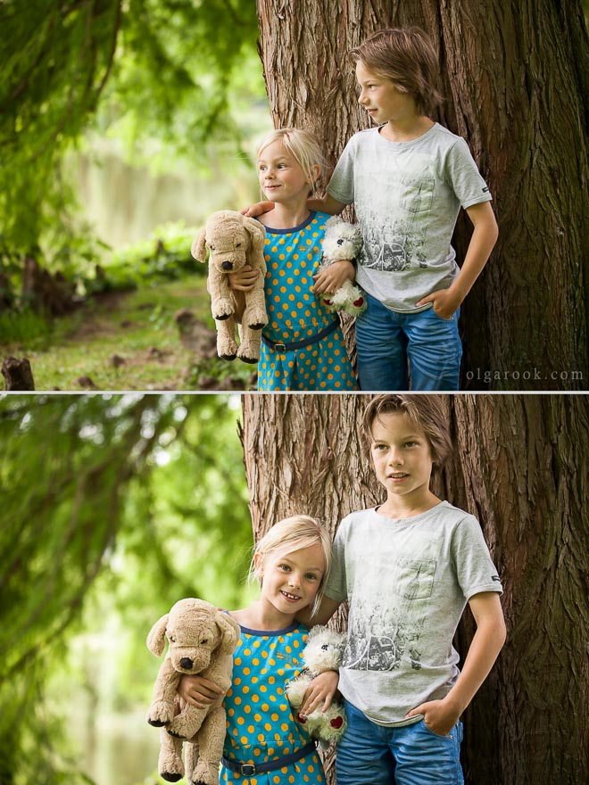 Portait of a boy and his younger sister standing under a big tree in a forest