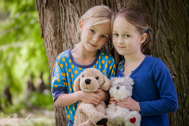 A dreamy and romantic portrait of two little girls standing under a big tree and holding their stuffed toys in their hands.