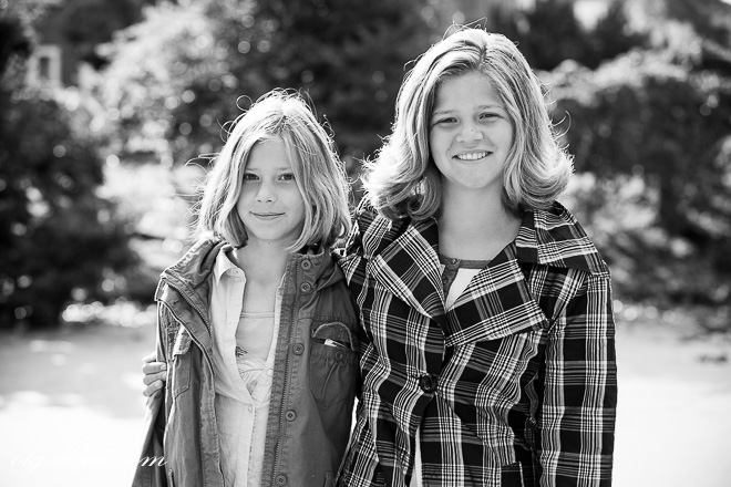 Black and white portrait of two teenage sisters in a park