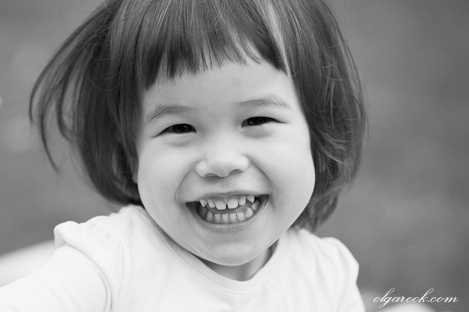 Black and white portrait of a small girl laughing