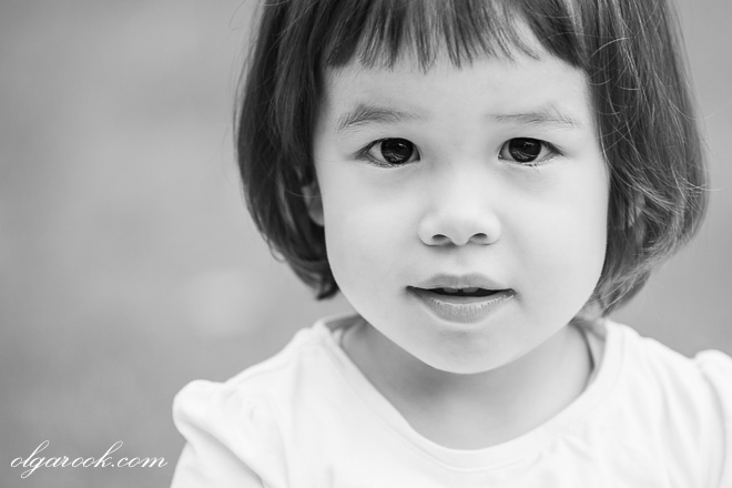 Black and white outdoor portrait of a little dark-eyed girl