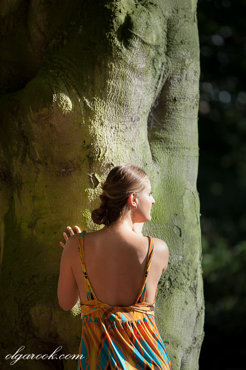 Portrait of a woman next to a large tree in sharp sunlight: you can almost sense the heat