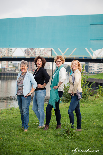 Four elegant ladies posing in front of the bridge.
