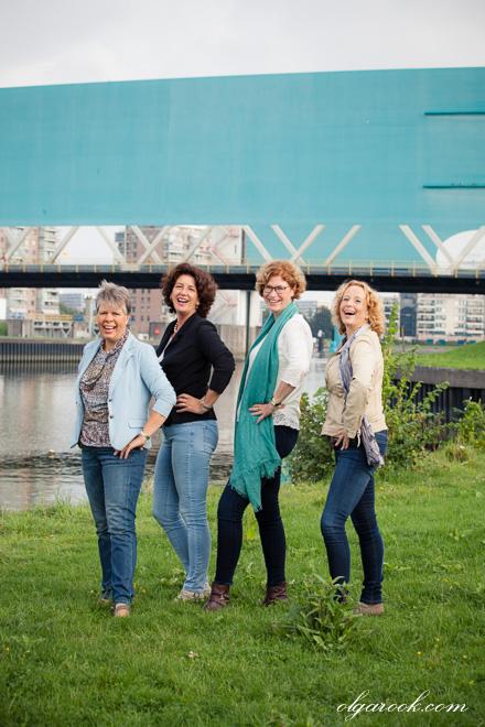 Vier dames poseren voor een brug