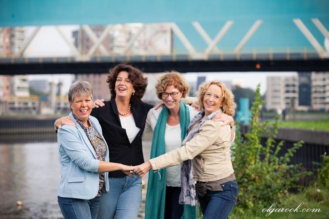 Vier dames die lachend elkaar omhelzen.