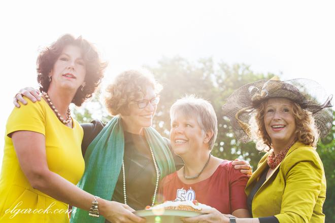 Foto van vier elegante dames die een feest met een gebak vieren