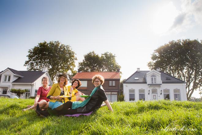 Een kleurenfoto van een groep elegante dames die aan het picknicken zijn.