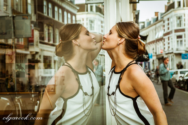 Color portrait of a woman kissing her reflection in a shop window.