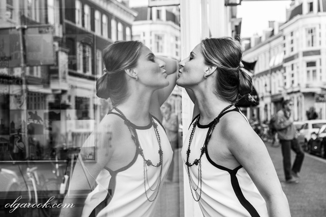 Artistic black and white street portrait of a young woman about to kiss her own reflection in a shop window.