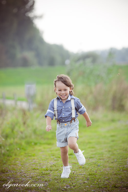 A dreamy photo of a laughing little boy running through a field