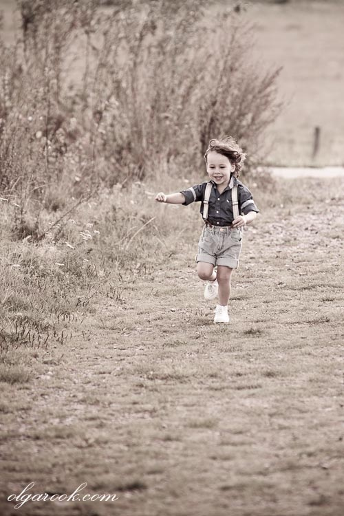 A nostalgic photo of a little boy running through a field