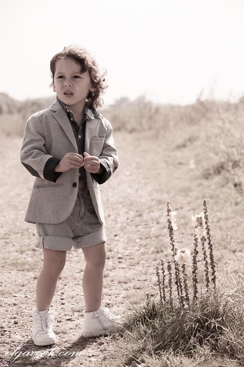 A romantic photo of a little boy dressed in retro style clothes in a field