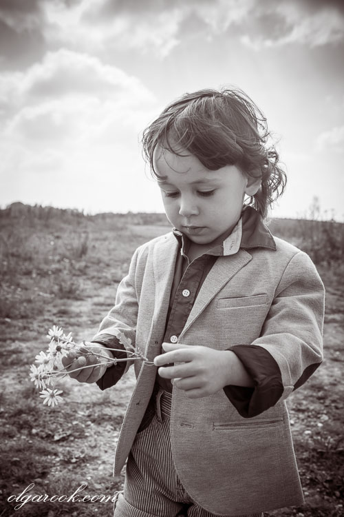Retro style romantic portrait of a little boy with a field flower in his hands