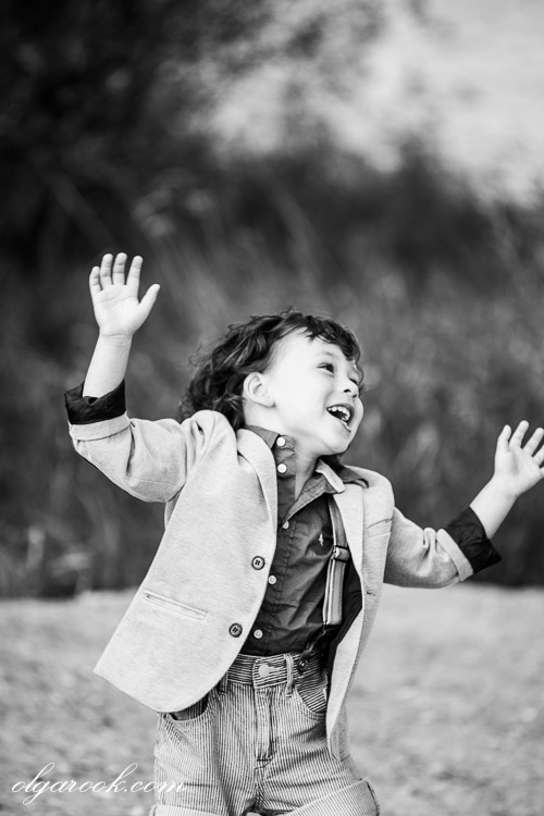 Black and white image of a laughing little boy who jumps and dances out of joy.