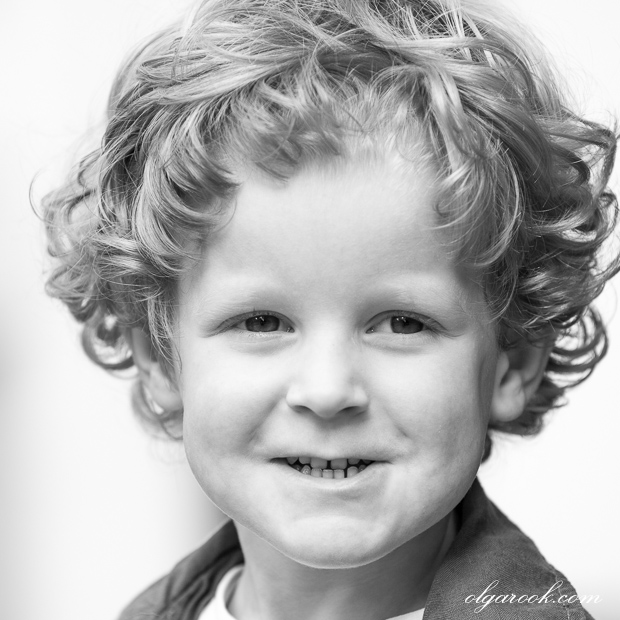 classic black and white portrait of a little curly boy with an impish smile