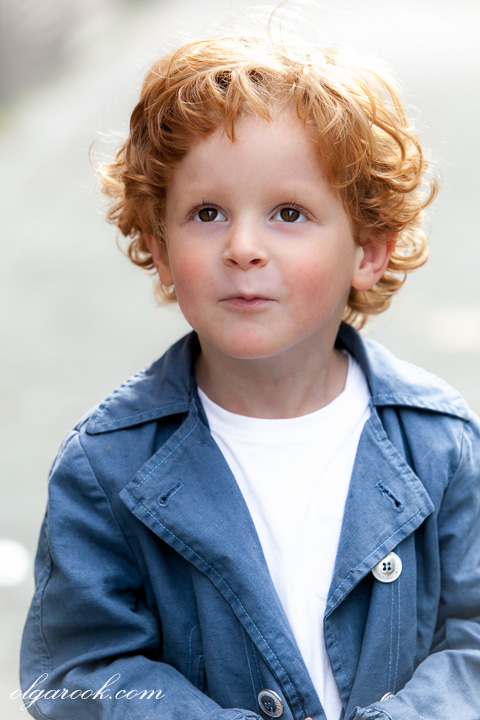 Photo of a little curly boy with a sarcastic smile