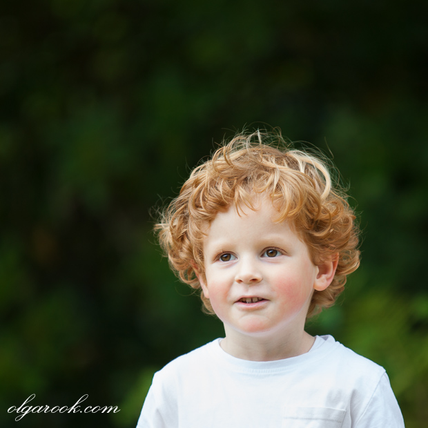 Portrait of a red-haired little boy in a park