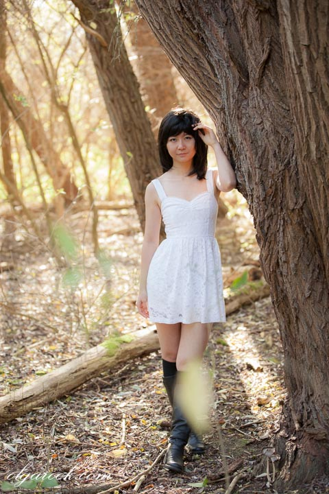 photo of girl in an autumn forest: she wears a short white dress