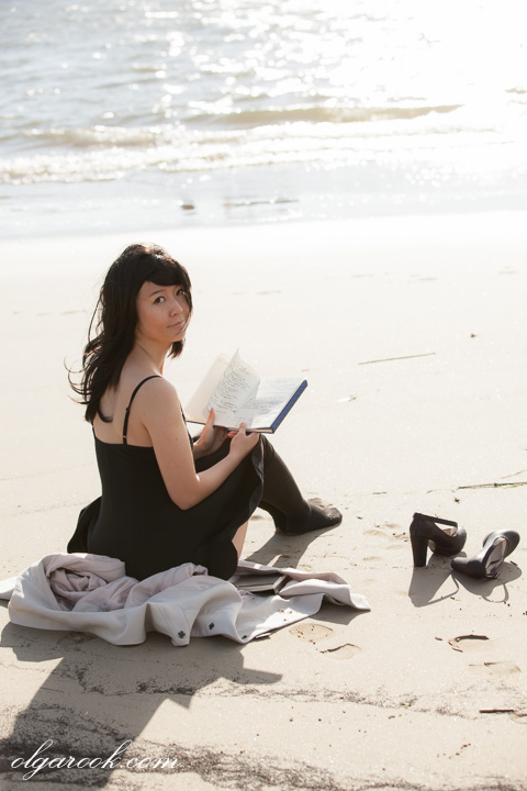 romantic and dreamy portrait of a girl reading a book on a beach