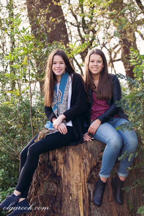 photo of two girls sitting on a trunk of tree in a forest