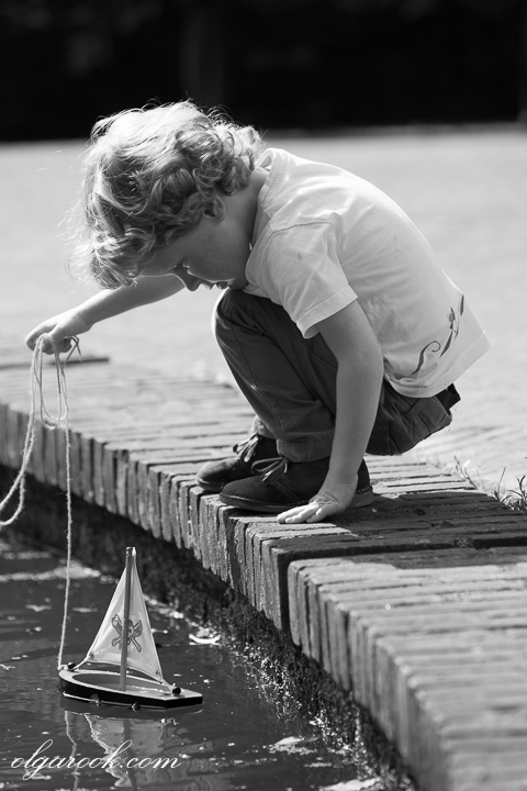 black and white nostalgic portrait of a child playing with a toy boat