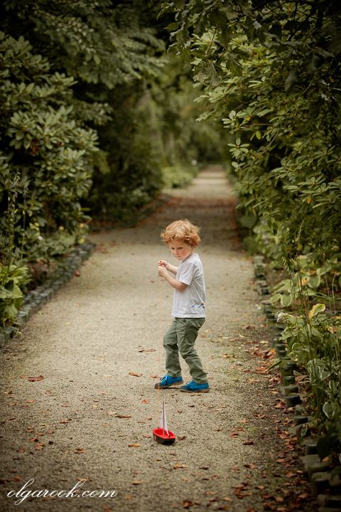 nostalgic painterly photo of a little boy playing on an alley of a park
