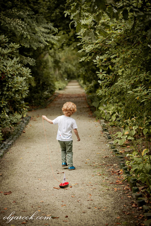 nostalgic photo of a little boy playing on a path in a park