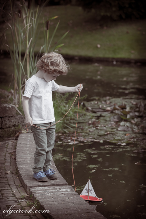 dreamy retro-like photo of a little boy with a toy boat