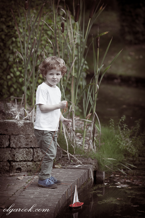 portrait of a little boy with a toy boat at a lake