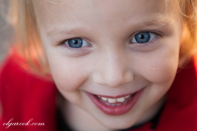 A close-up portrait of a little girl with blue eyes