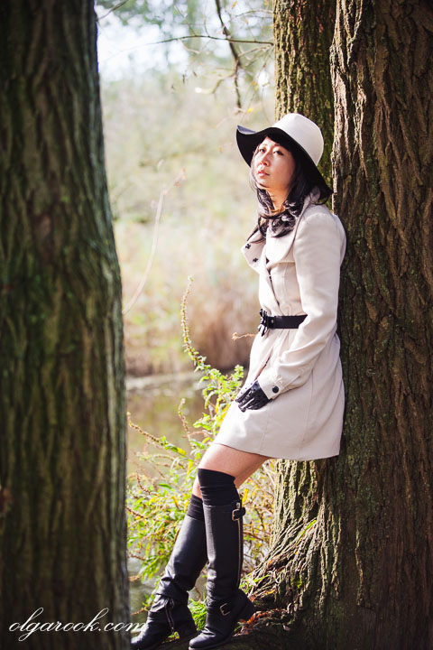 romantic photo of a girl wearing a hat and leaning against a tree in a wood