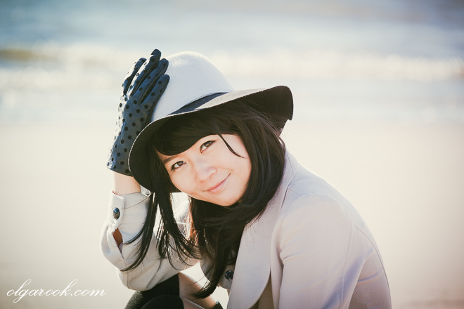 Dreamy and romantic portrait of a cute and elegantly dressed girl with a sweet smile. The girl is sitting on a beach with the sea sparkling behind her.