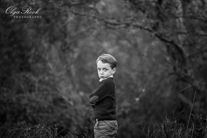 Moody portrait of an angry-looking little boy in a wood