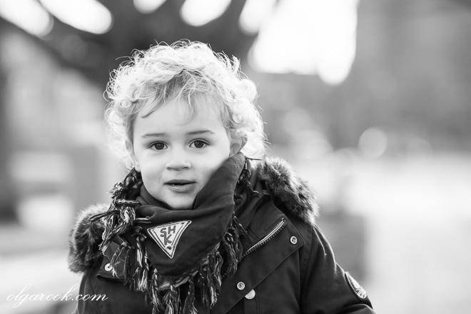 portrait of a little blond boy walking in a park in winter