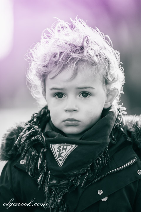Portrait of a tough looking little boy: his hair, expression and clothes recall the style of the eighties.