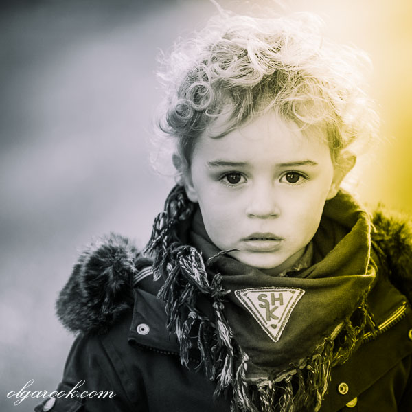 Artistic portrait of a little boy with blond curls and expressive dark eyes. His expression recalls the images of the rock stars from the late eighties.