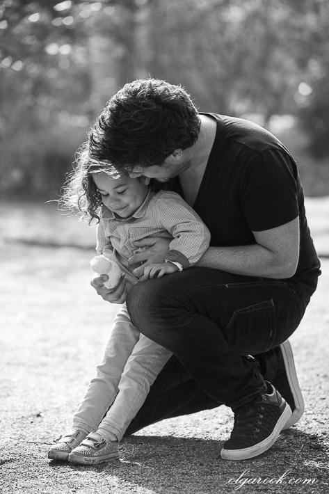 photo of a little girl playing with her father in a park