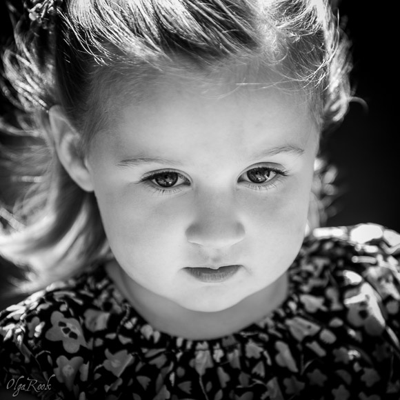 Artistic portrait of a little girl with a serene expression on her face.