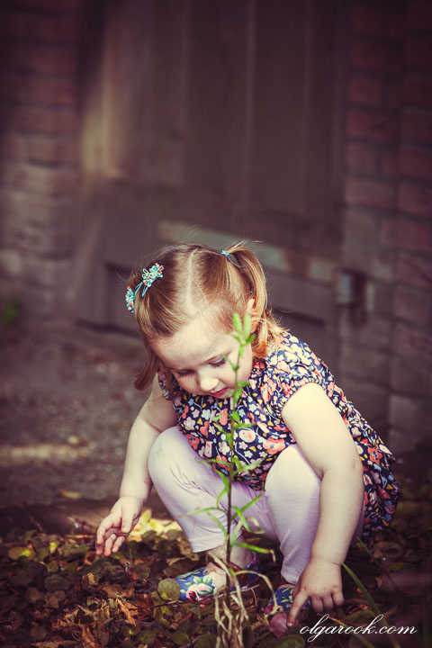Dreamy portrait of a little girl playing a garden.
