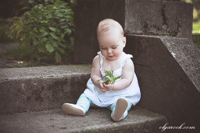 Portrait of an angelically quiet baby sitting on the stone stairs in a park playing with little flowers