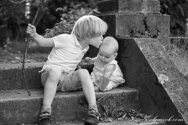 Foto van een klein jongetje die een zoen aan zijn baby zusje geeft