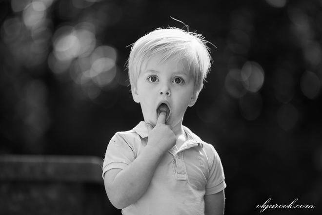 A funny photo of a little boy holding his finger in his open mouth