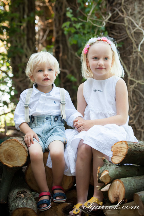 Dreamy portrait of two little children sitting in a forest on a pile of wood